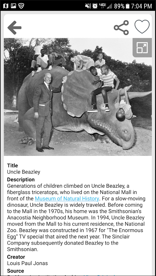 Mockup of how a single item displays on the mobile app. There is an older white man leaning against a large fiberglass triceratops. Seven children sit on the triceratops. Below the image is a display of Dublin Core metadata for the image.